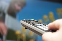 Hand holding TV remote control. Stock Photos