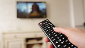 Hand holding TV remote control and changing channels on television. stock video footage