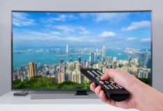 Hand holding TV remote control with a television and city screen Royalty Free Stock Image