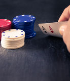 Hand holding two aces, poker chips, retro color look. With split toning, dark slate surface as underground, shallow depth of field Royalty Free Stock Photo