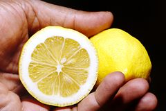 Hand holding two halves of a lemon Royalty Free Stock Photos