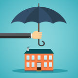 Hand holding umbrella over a house Stock Image