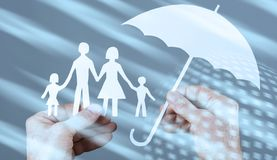 Family protection coverage concept with light effect. Hand holding an umbrella protecting a family with light effect stock photo
