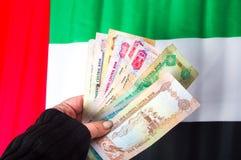 Hand holding United Arab Emirates dirhams. On top of flag stock photo
