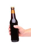 A hand holding up a brown beer bottle. Without label over a white background vertical format Stock Photography