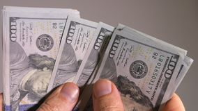 Hand holding up and counting US 100-dollar bills stock video footage