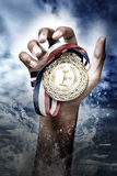 Hand holding up a gold medal. As a winner in a competition Royalty Free Stock Photos