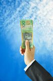 Hand holding up money - Australian dollars - on blue sky background Royalty Free Stock Photography