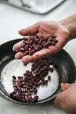 Hand holding up palm, black beans over frying pan Stock Photo