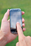 Hand holding and using smart mobile phone. Outside shot of a hand holding smart phone Royalty Free Stock Photo