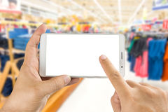 Hand holding and using smart phone with blurred image shopping in supermarket. Man hand holding and using smart phone with isolated screen with blurred image Stock Photos