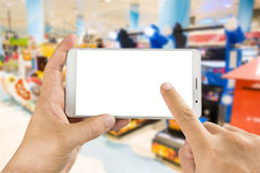 Hand holding and using smart phone with  screen with. Man hand holding and using smart phone with  screen with blurred image of game zone in supermarket Royalty Free Stock Images