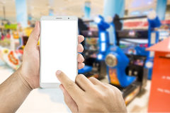 Hand holding and using smart phone with  screen with. Man hand holding and using smart phone with  screen with blurred image of game zone in supermarket Royalty Free Stock Image
