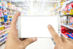 Hand holding Using smart phone in supermarket. Using smart phone in supermarket Stock Image