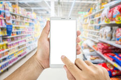 Hand holding Using smart phone in supermarket. Man hand holding Using smart phone in supermarket Stock Photography