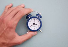 Time concept. Hand holding vintage alarm clock Royalty Free Stock Photos