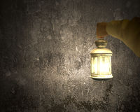 Hand holding vintage lamp illuminating dark concrete wall Royalty Free Stock Images