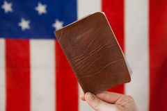 Hand holding a visa against American flag. Close-up of hand holding a visa against American flag stock images