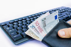 Hand holding wallet with money at keyboard Royalty Free Stock Photos
