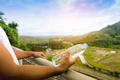 Hand holding water bottle and background of nature view. 1 Stock Photography
