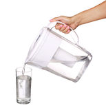 Hand holding water filter jug and pouring water into a glass Royalty Free Stock Images