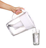 Hand holding water filter jug and pouring water into a glass Royalty Free Stock Photos