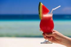 Hand holding watermelon cocktail on the beach Stock Photos