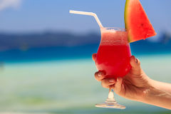 Hand holding watermelon cocktail on beach Royalty Free Stock Photos