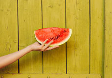 Hand Holding Watermelon Slice on Green Wooden Background Stock Photo