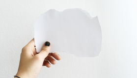 Hand holding a white blank paper. A hand of a casual person, holding a white blank paper, on white background Royalty Free Stock Images