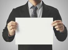 Hand holding white blank paper sheet. Mockup Stock Photo