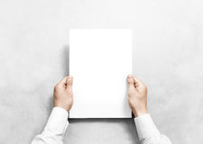 Hand holding white blank paper sheet mockup, . Stock Image