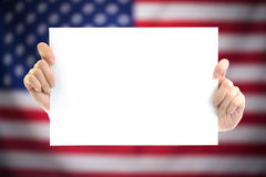 Hand holding white blank paper sheet mockup with US flag blurred stock photography