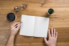 Hand holding white blank paper sheet mockup on wooden background royalty free stock photography
