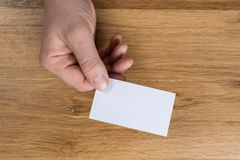 Hand holding white blank paper sheet mockup on wooden background royalty free stock image
