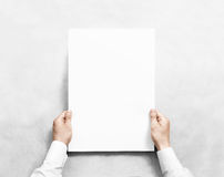 Hand holding white blank poster mockup, isolated. Arm in shirt hold clear broadsheet template mock up. Affiche bill surface design. Broadside pure print Royalty Free Stock Photos
