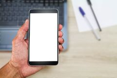 Hand holding white blank screen smartphone above blurred office wooden desk with laptop computer,paper and pens Royalty Free Stock Photos