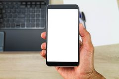 Hand holding white blank screen smartphone above blurred office wooden desk with laptop computer,paper and pens Stock Image
