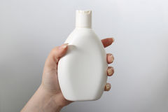 Hand holding white bottle on the white background horisontal. Hand holding white bottle on the white background. horisontal Stock Photos
