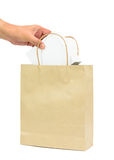 Hand holding a white box in brown paper shopping bag Royalty Free Stock Photography