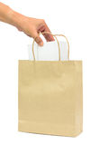 Hand holding a white box in brown paper shopping bags. Stock Images