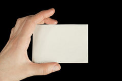 Hand holding a white card. Isolated on black background Royalty Free Stock Photography