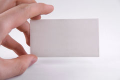 Hand holding white card. Hand golding paper card on white background Stock Photo