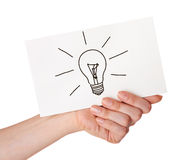Hand holding a white card with light bulb Royalty Free Stock Photo