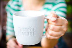 Hand holding White ceramic mug with stamp word. Taste of nature at coffee shop Royalty Free Stock Photo