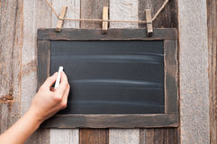 Hand holding white chalk on blank blackboard Royalty Free Stock Images