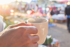 Hand holding white coffee cup on fresh food maket. Royalty Free Stock Photos