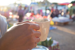 Hand holding white coffee cup on fresh food maket. Royalty Free Stock Images