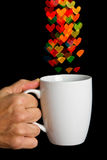 Hand holding white cup with bokeh heart shapes Stock Photos