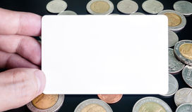Hand holding card on top of coins. Hand holding white dummy card (to be replaced with your own) on top of Thai coins Stock Images